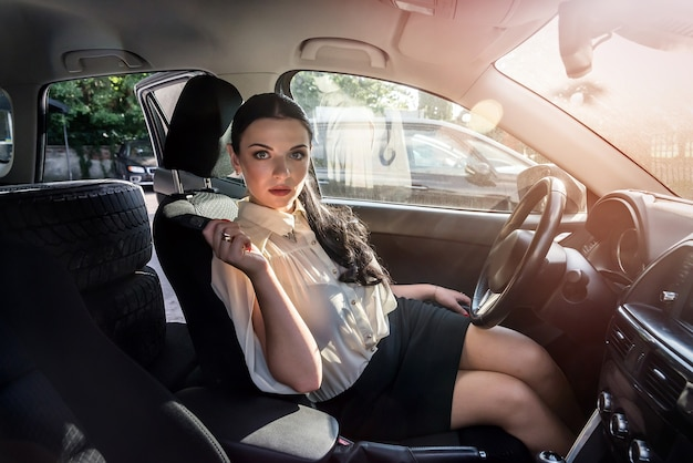 Attractive brunette sitting inside car and showing key