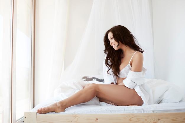 Привлекательная брюнетка, сидящая на своей кровати