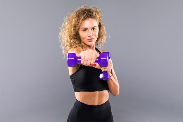 Привлекательная спортивная женщина брюнетки в черной спортивной одежде держит гантели, изолированные на серой стене.