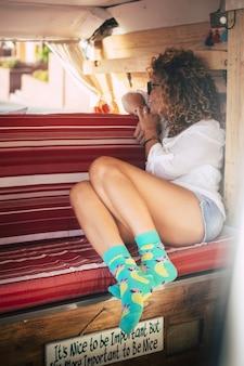魅力的なブルネットの旅行の女性は、外を見て少し居心地の良いレトロなミニバンの中に座っています
