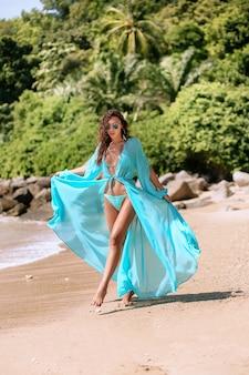 ビーチで青いビキニと青いマントでポーズをとるスリムなボディと長い脚を持つ魅力的なブルネット