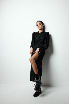 明るいメイクで魅力的なブルネットファッショナブルなモダンな服の黒いブーツ