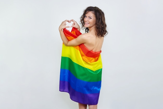An attractive brunette with an lgbt flag folded her hands in the shape of a heart