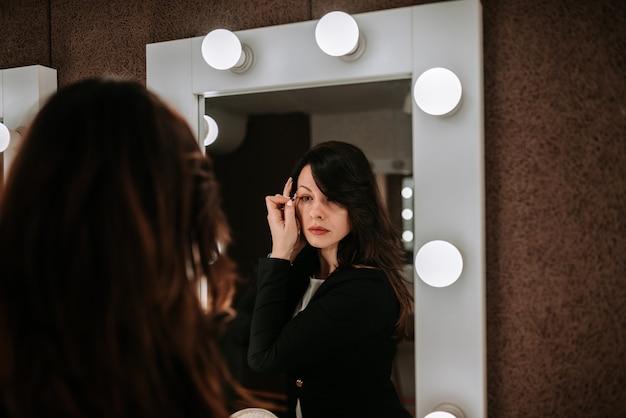 Attractive brunette woman applying eyeliner.