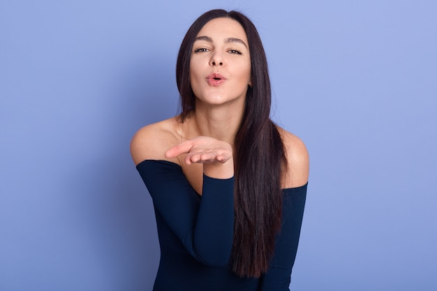Attractive brunette woman blowing kiss at camera on blue, young female model wearing elegant dress posing with bare shoulders, attractive girl with perfect skin and long staraight hair