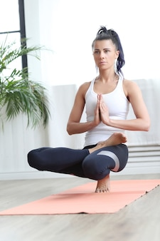 Attractive brunette woman doing yoga at home.