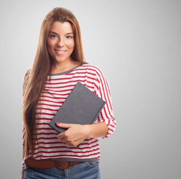 黒のノートブックを保持している魅力的なブルネットの女性