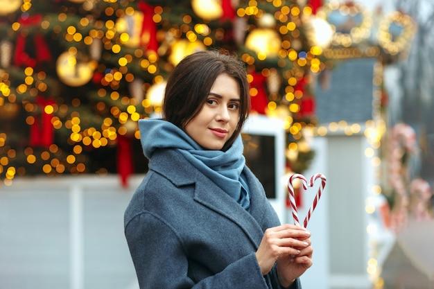 ハートの形でキャンディーを保持している魅力的なブルネットの女性