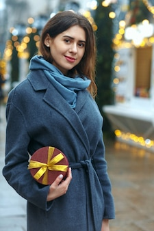 Attractive brunette woman holding gift box near the christmas fair