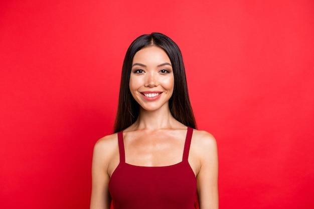 Привлекательная брюнетка женщина в красном платье позирует у красной стены