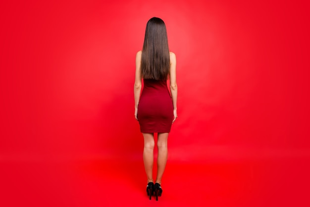 빨간 벽에 포즈 빨간 드레스에 매력적인 갈색 머리 여자