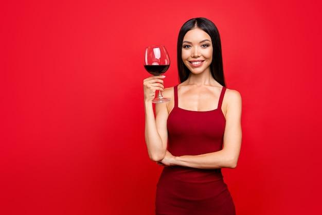 赤い壁にポーズをとって赤いドレスを着た魅力的なブルネットの女性