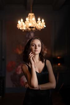 シャンデリアとデザイナーの部屋でポーズをとって黒い絹のドレスの魅力的なブルネットの女性