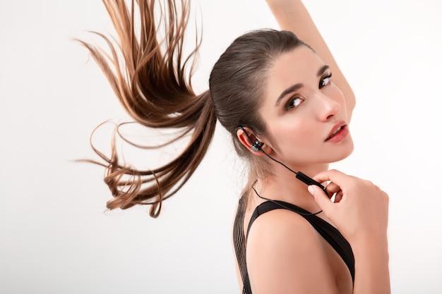 Привлекательная брюнетка женщина в беговой трусцой черном топе, слушать музыку в наушниках, позирует изолированной на белой стене