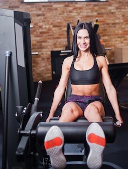 체육관에서 운동 기계에서 다리 확장 운동을하는 운동복에 매력적인 갈색 머리 여자