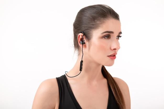 Attractive brunette woman in jogging black top listening to music on earphones posing
