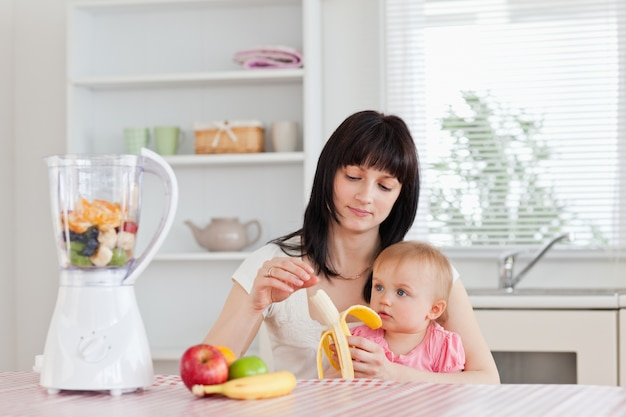 Attractive brunette woman pealing a banana while holding her baby on her knees in the kitchen