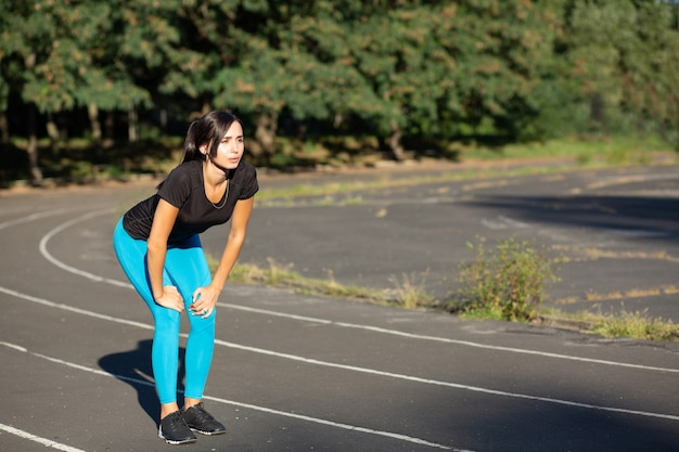Attractive brunette woman running on the daylight on the jogging track. space for text