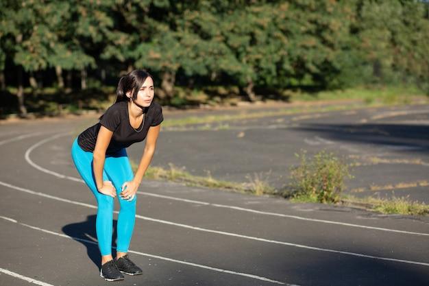 ジョギングコースで日光の下で走っている魅力的なブルネットの女性。テキスト用のスペース