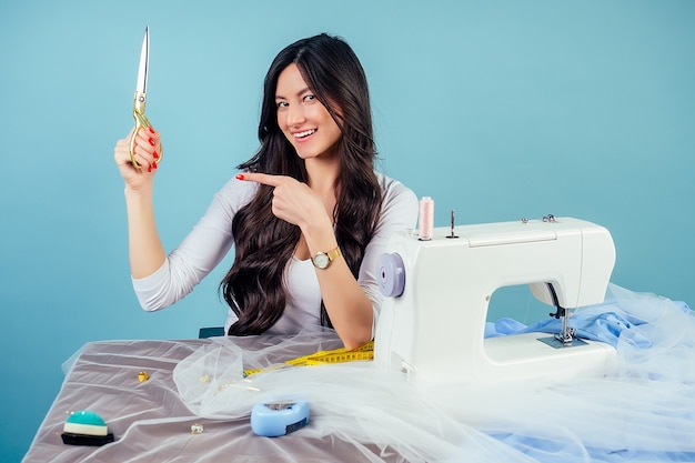 魅力的なブルネットの女性の裁縫師の仕立て屋(洋裁)は、スタジオの青い背景にミシンでハサミを持ってテーブルの生地をカットします。