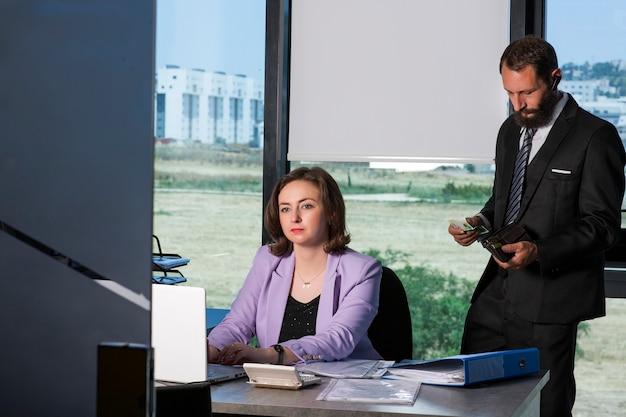 魅力的なブルネットの女性がオフィスの机に座っています。彼女の前にはラップトップがあり、後ろに男性の同僚が立っている書類が入った電卓が財布にお金を入れています。ビジネスアイデアの概念