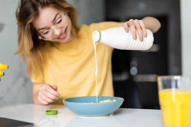 Привлекательная брюнетка женщина улыбается и наливает молоко в миску с дубовыми хлопьями