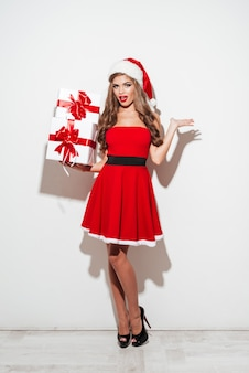 Attractive brunette woman standing with heap of gift boxes isolated