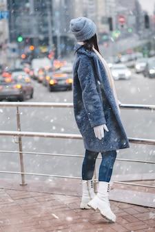 魅力的なブルネットの女性は、降雪時の夕方に街の交通を見て流行の冬のコートと帽子を身に着けています