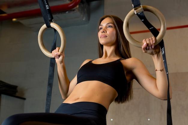 美しい体を持つ魅力的なブルネットの女性は、ジムで手の運動を行います