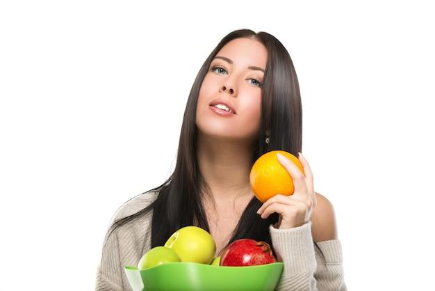 과일 그릇으로 매력적인 갈색 머리 여자
