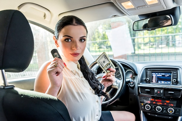 Attractive brunette woman with car key posing inside car