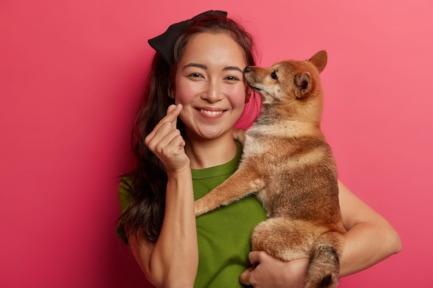 Attractive brunette woman with eastern appearance, holds shiba inu dog on hands, makes korean like sign, expresses love to pet, adopts animal