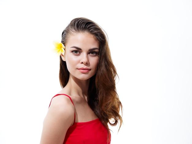 髪の正面図に花を持つ魅力的なブルネットの女性