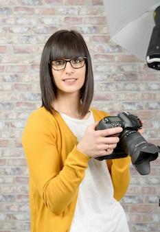Attractive brunette woman with photo camera in studio