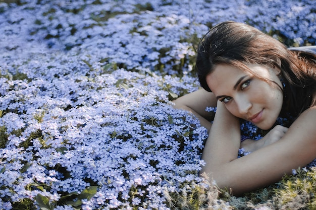 Attractive brunette woman with sexy look is lying on the yard with blue flowers