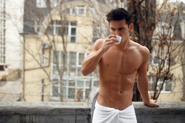 コーヒーのカップを飲んで、バスルームのタオルで魅力的なブルネット若い裸の男