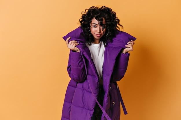 紫色のダウンジャケットでポーズをとる魅力的なブルネットの若い女性