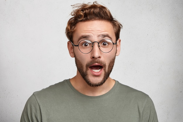 Attraente uomo hipster dagli occhi bug o studente intelligente in maglietta casual, urla scioccato,