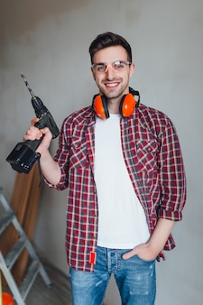 Attractive builder n eyeglasses and with a drill in his hands