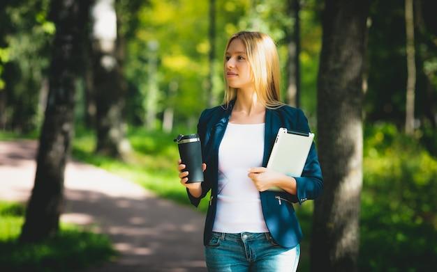 公園でコーヒーを飲みながら彼女のタブレットを使用して魅力的なビジネスの少女