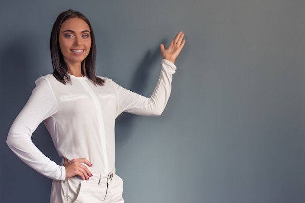 Attractive business lady is standing on gray background with copyspace