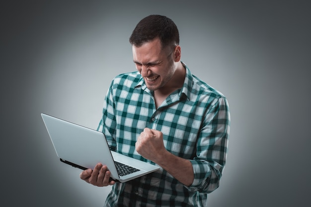 ラップトップで作業し、左手で何かを示す灰色で分離された緑のシャツの魅力的なビジネスマンモデル。