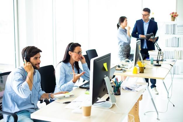 Привлекательные деловые люди в наушниках улыбаются, работая с компьютером в современном офисе