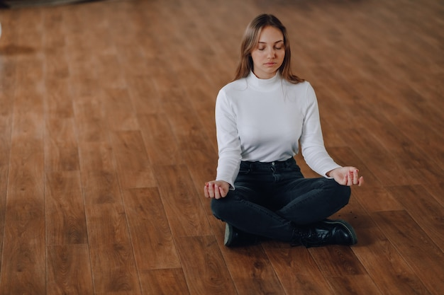 魅力的なビジネススタイルの女の子は、蓮華座の床に座っています。オフィスでのヨガ、仕事でのリラクゼーション。ビジネスライフの調和を求めて。ヨガと調和のとれた肯定的な心の状態。