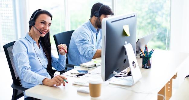 Привлекательная деловая женщина и деловой человек с наушниками улыбаются, работая с компьютером в офисе