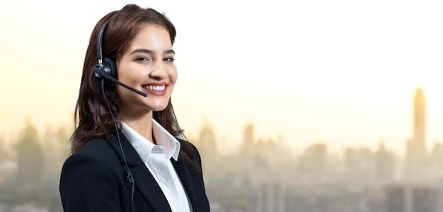 매력적인 비즈니스 우먼과 헤드셋이 일하는 동안 웃고 있습니다. 고객 서비스 조수가 일하는 동안