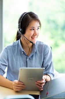 Привлекательная бизнес-леди азиатка в костюмах и гарнитурах улыбаются, работая с компьютером в офисе. помощник по работе с клиентами, работающий в офисе