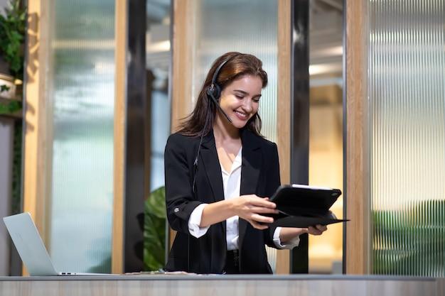 スーツとヘッドセットを着たアジア系の魅力的なビジネスウーマンが、コンピューターを操作しながら微笑んでいる