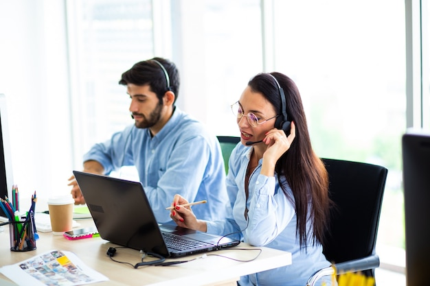 Attractive business woman and business man with headsets are smiling while working with computer in office