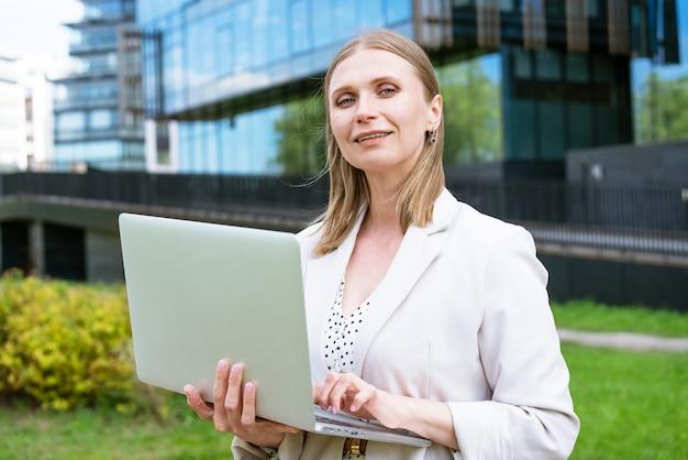 Привлекательная деловая женщина успеха в бизнесе очаровательная красивая женщина держит ноутбук молодая женщина ...
